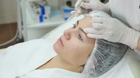 Ο γιατρός επισύρει την προσοχή τις γραμμές με το δείκτη στο υπομονετικό πρόσωπο για την του προσώπου πλαστική χειρουργική στην κλ απόθεμα βίντεο