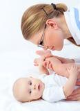 Ο γιατρός θεραπόντων στα γυαλιά ασκεί το μικρό μωρό Στοκ εικόνες με δικαίωμα ελεύθερης χρήσης