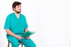 Ο γιατρός κάθεται σε μια καρέκλα με το φάκελλο σε ένα άσπρο υπόβαθρο Στοκ φωτογραφία με δικαίωμα ελεύθερης χρήσης