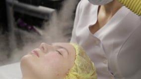 Ο γιατρός καθαρίζει το δέρμα της γυναίκας με έναν ατμό νέα γυναίκα με το δέρμα προβλήματος στο beautician Cosmetology έννοια απόθεμα βίντεο