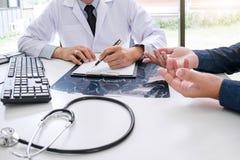 Ο γιατρός καθηγητή συστήνει την έκθεση μια μέθοδος με την υπομονετική θεραπεία, τα αποτελέσματα εξετάζουν επάνω μια των ακτίνων X στοκ εικόνες με δικαίωμα ελεύθερης χρήσης
