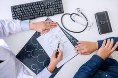 Ο γιατρός καθηγητή συστήνει την έκθεση μια μέθοδος με την υπομονετική θεραπεία, τα αποτελέσματα εξετάζουν επάνω μια των ακτίνων X στοκ φωτογραφία με δικαίωμα ελεύθερης χρήσης