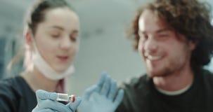Ο γιατρός κινηματογραφήσεων σε πρώτο πλάνο με τα μπλε γάντια που παρουσιάζουν μια σκάφη με κάποια ιατρική στον ασθενή του και εξη απόθεμα βίντεο