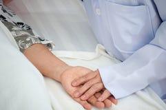 Ο γιατρός κινηματογραφήσεων σε πρώτο πλάνο παίρνει τον υπομονετικό ύπνο γιαγιάδων χεριών λαβής προσοχής στο ηλικιωμένο σπίτι στοκ εικόνες