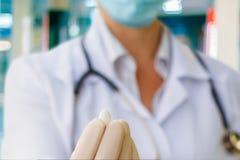Ο γιατρός κρατά ένα χάπι που μεταχειρίζεται στοκ φωτογραφίες με δικαίωμα ελεύθερης χρήσης