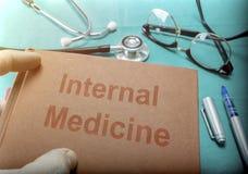 Ο γιατρός κρατά το βιβλίο στην εσωτερική ιατρική σε ένα νοσοκομείο στοκ εικόνες