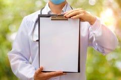 Ο γιατρός κρατά το φύλλο των υποθέσεων στα χέρια στοκ φωτογραφία