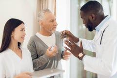 Ο γιατρός λέει στη νοσοκόμα πώς ένας ηλικιωμένος αρσενικός ασθενής πρέπει να πάρει τα χάπια Στοκ Εικόνες