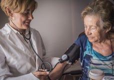 Ο γιατρός μετρά την αρτηριακή ένταση στο oldster στο σπίτι Στοκ φωτογραφία με δικαίωμα ελεύθερης χρήσης
