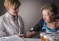 Ο γιατρός μετρά την αρτηριακή ένταση στο oldster στο σπίτι Στοκ Εικόνα