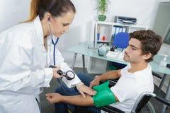 Ο γιατρός μετρά τον υπομονετικό νεαρό άνδρα πίεσης του αίματος Στοκ Εικόνες