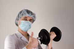 Ο γιατρός νεαρών άνδρων κρατά dambbell σε ένα χέρι και παρουσιάζει όπως στο ουδέτερο υπόβαθρο Έννοια Medcine και αθλητισμού Στοκ Εικόνα