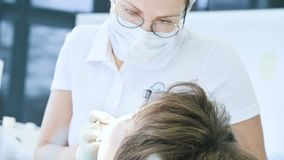 Ο γιατρός οδοντιάτρων γυναικών στη μάσκα γυαλιών και την άσπρη ΚΑΠ εξετάζει τη στοματική κοιλότητα του ασθενή Εργασία οδοντιάτρου φιλμ μικρού μήκους
