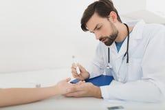 Ο γιατρός παίρνει ένα δείγμα αίματος από το αγόρι για να το ελέγξει για τη ζάχαρη Το αγόρι υπομένει υπομονετικά τη διαδικασία Στοκ φωτογραφίες με δικαίωμα ελεύθερης χρήσης
