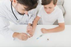 Ο γιατρός παίρνει ένα δείγμα αίματος από το αγόρι για να το ελέγξει για τη ζάχαρη Το αγόρι υπομένει υπομονετικά τη διαδικασία Στοκ Εικόνα