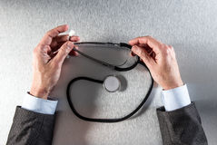 Ο γιατρός παραδίδει την αντανάκλαση που κρατά ένα στηθοσκόπιο για την κλινική επεξεργασία Στοκ Φωτογραφία