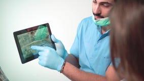 Ο γιατρός παρουσιάζει ακτίνα X δοντιών στην ταμπλέτα φιλμ μικρού μήκους