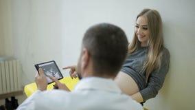 Ο γιατρός παρουσιάζει μια εικόνα ενός υπερήχου σε μια ταμπλέτα σε μια έγκυο γυναίκα απόθεμα βίντεο