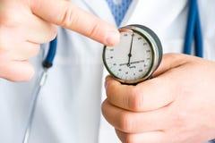 Ο γιατρός παρουσιάζει στον ασθενή και δείχνει το δάχτυλο στο βέλος του μηχανικού sphygmomanometer, το οποίο δείχνει με τη σειρά τ στοκ φωτογραφία με δικαίωμα ελεύθερης χρήσης