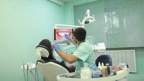 Ο γιατρός παρουσιάζει στο όργανο ελέγχου υγιή δόντια του ασθενή φιλμ μικρού μήκους