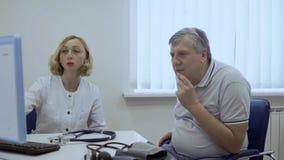 Ο γιατρός παρουσιάζει τα αποτελέσματα της δοκιμής στον υπολογιστή σε έναν ηληκιωμένο απόθεμα βίντεο