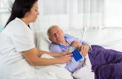 Ο γιατρός παρουσιάζει τον ασθενή πώς να χρησιμοποιήσει τα καθημερινά χάπια δόσεων στοκ φωτογραφία