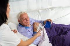 Ο γιατρός παρουσιάζει τον ασθενή πώς να χρησιμοποιήσει τα καθημερινά χάπια δόσεων στοκ εικόνες με δικαίωμα ελεύθερης χρήσης