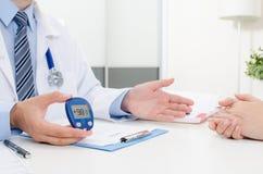 Ο γιατρός παρουσιάζει glucometer με το επίπεδο γλυκόζης στοκ εικόνες