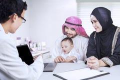 Ο γιατρός παρουσιάζει lap-top στην αραβική οικογένεια Στοκ Εικόνες