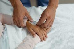 Ο γιατρός που συνδέει IV σταλαγματιά στον ασθενή παραδίδει το θάλαμο στο νοσοκομείο στοκ εικόνες με δικαίωμα ελεύθερης χρήσης