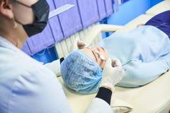Ο γιατρός σε ένα άσπρο παλτό και μια μαύρη μάσκα βουρτσίζει τα WI προσώπου του κοριτσιού στοκ εικόνα με δικαίωμα ελεύθερης χρήσης