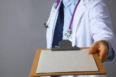 Ο γιατρός σε ένα άσπρο παλτό με ένα στηθοσκόπιο που κρατά έναν φάκελλο Στοκ φωτογραφία με δικαίωμα ελεύθερης χρήσης