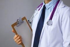 Ο γιατρός σε ένα άσπρο παλτό με ένα στηθοσκόπιο που κρατά έναν φάκελλο Στοκ εικόνες με δικαίωμα ελεύθερης χρήσης