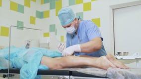 Ο γιατρός στα αποστειρωμένα ενδύματα προετοιμάζει τα ιατρικά εργαλεία και κάνει το πόδι ασθενών εγχύσεων πριν από τη λειτουργία φιλμ μικρού μήκους