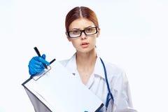 Ο γιατρός στα γυαλιά κρατά μια ταμπλέτα φακέλλων, εργασία στο νοσοκομείο Στοκ Φωτογραφίες