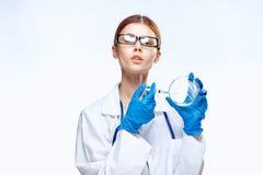 Ο γιατρός στα γυαλιά σε μια ιατρική εσθήτα επιδέσμου κρατά ένα petri πιάτο, εργαστηριακά γυαλικά, ιατρική Στοκ εικόνες με δικαίωμα ελεύθερης χρήσης