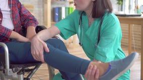 Ο γιατρός στην κλινική εξετάζει το πόδι ενός έφηβη με ειδικές ανάγκες σε μια αναπηρική καρέκλα απόθεμα βίντεο