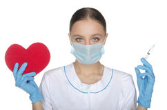 Ο γιατρός στη μάσκα παρουσιάζει ένα σύμβολο και σύριγγα καρδιών Στοκ φωτογραφίες με δικαίωμα ελεύθερης χρήσης