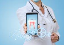 Ο γιατρός στο τηλέφωνο app παρουσιάζει την επεξεργασία των δοντιών Στοκ Εικόνες