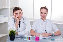 Ο γιατρός τύπων και κοριτσιών στην ομοιόμορφη συνεδρίαση στο γραφείο και το χαμόγελο indoors στοκ εικόνα
