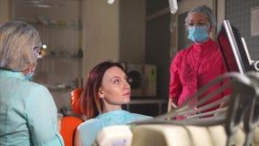 Ο γιατρός Orthodontist λέει στον ασθενή τι θα κάνει με τα δόντια στην οδοντιατρική απόθεμα βίντεο