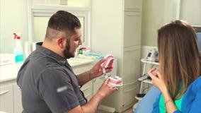 Ο γιατρός Ortodont λέει σε μια νέα γυναίκα για τις μεθόδους προσθετικής των δοντιών απόθεμα βίντεο