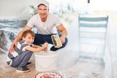 Ο γιος βοηθά τον πατέρα να ανακαινίσει και να χρωματίσει στοκ φωτογραφίες