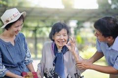 Ο γιος και η κόρη στο νόμο δίνουν ένα παρόν στην ηλικιωμένη μητέρα στοκ φωτογραφία με δικαίωμα ελεύθερης χρήσης