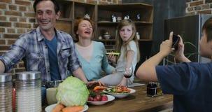 Ο γιος παίρνει τη φωτογραφία του γονέα και η αδελφή στην κουζίνα που χρησιμοποιεί το έξυπνο τηλέφωνο κυττάρων κάνει το πορτρέτο τ φιλμ μικρού μήκους