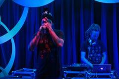 Ο γιόγκη MC κρατά παραδίδει το μέτωπο του προσώπου με το DJ Drez πίσω από τον Στοκ Εικόνες