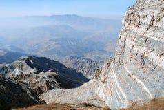 Ο γκρίζος βράχος σε ένα υπόβαθρο ενός πανοράματος των βουνών της Τιέν Σαν στοκ φωτογραφία με δικαίωμα ελεύθερης χρήσης