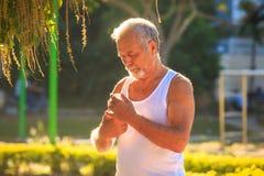 Ο γκρίζος γενειοφόρος ηληκιωμένος στη φανέλλα κρατά το μπουκάλι νερό στο πάρκο Στοκ Φωτογραφία