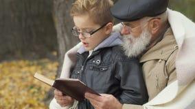 Ο γκρίζος-μαλλιαρός παππούς διάβασε με λίγο εγγονό στο πάρκο φθινοπώρου απόθεμα βίντεο