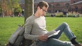 Ο γοητευτικός έξυπνος τύπος κάθεται στο δέντρο και διαβάζει κοντά στο πανεπιστήμιο φιλμ μικρού μήκους